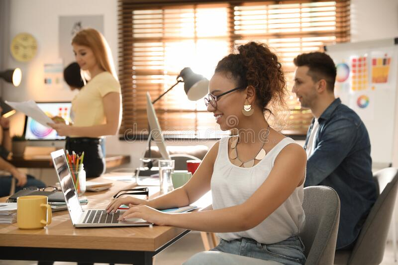 Happy female designer working with laptop. In office stock photos