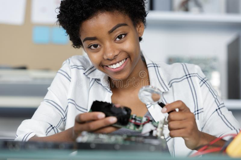 Happy female digital electronic engineer examining computer pc in laboratory royalty free stock images