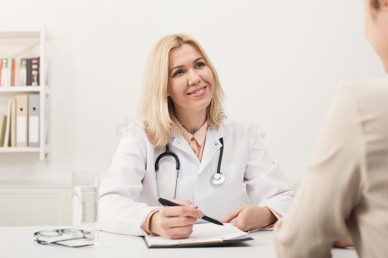 Happy doctor consulting woman in hospital stock image