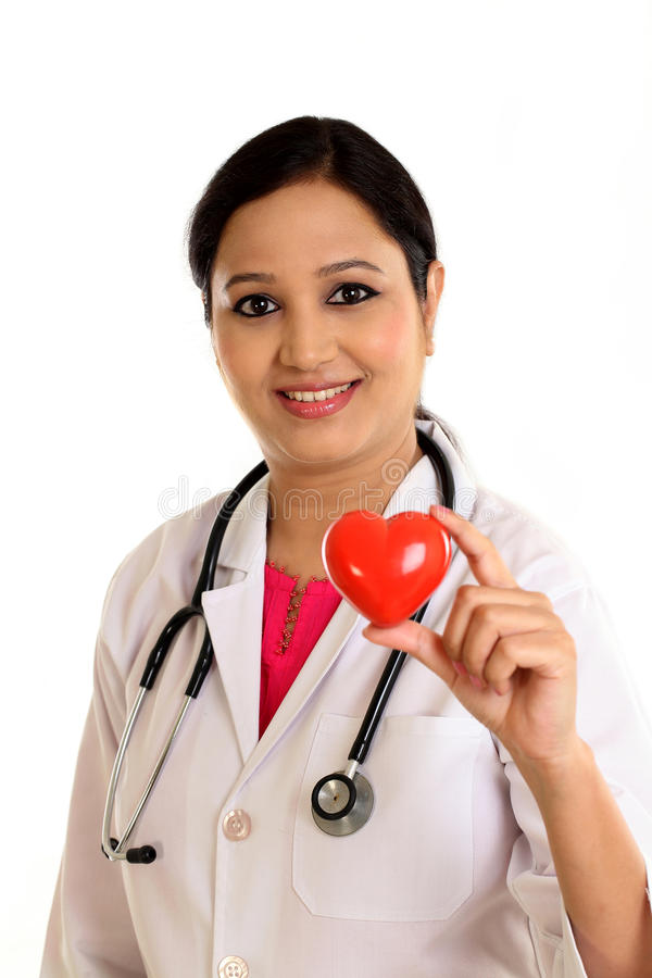 Happy female doctor holding a beautiful red heart shape. Happy young female doctor holding a beautiful red heart shape stock photo