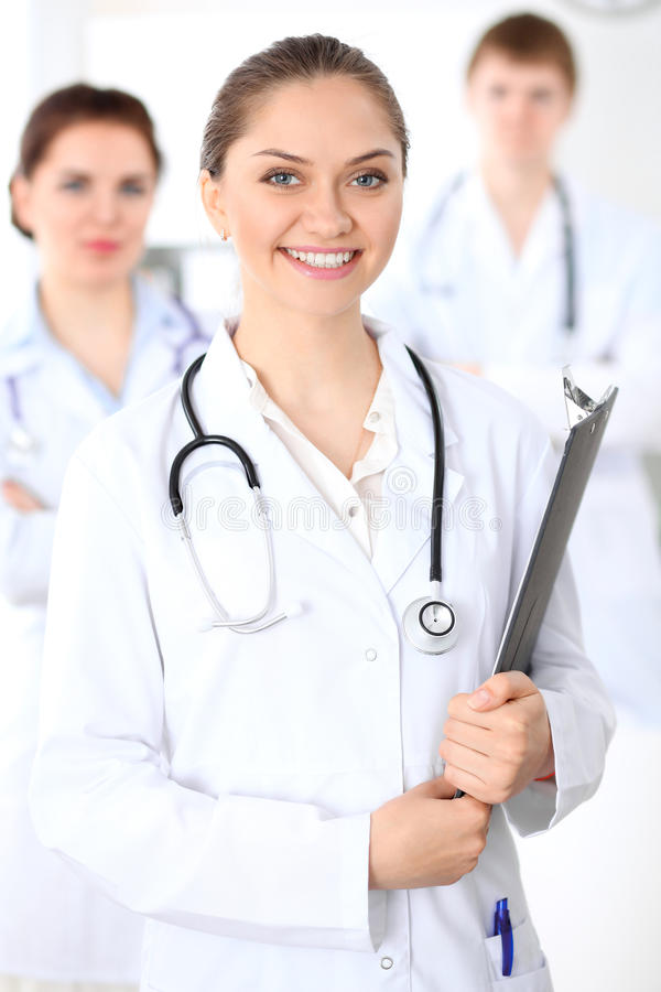 Happy female doctor keeping medical clipboard while medical staff are at the background. Successful team at health care and medicine concept stock photos