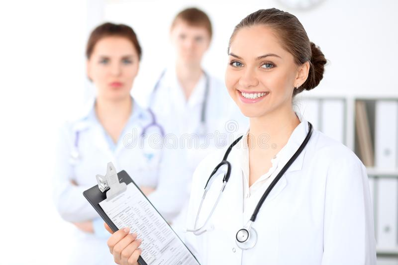 Happy female doctor keeping medical clipboard while medical staff are at the background. Successful team at health care and medicine concept royalty free stock photography