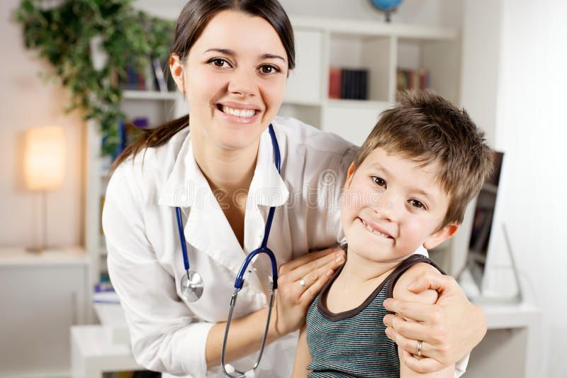 Happy female doctor with kid patient looking camera smiling. Cute kid with female doctor smiling stock images