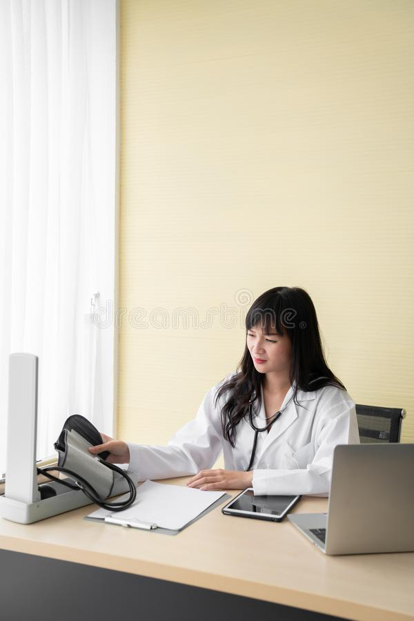 The happy female doctor sat on the working chair while set up blood pressure monitor in the examination room.  stock photos