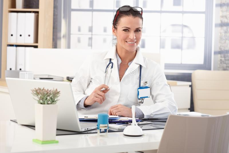 Happy female doctor sitting at medical office desk stock photo