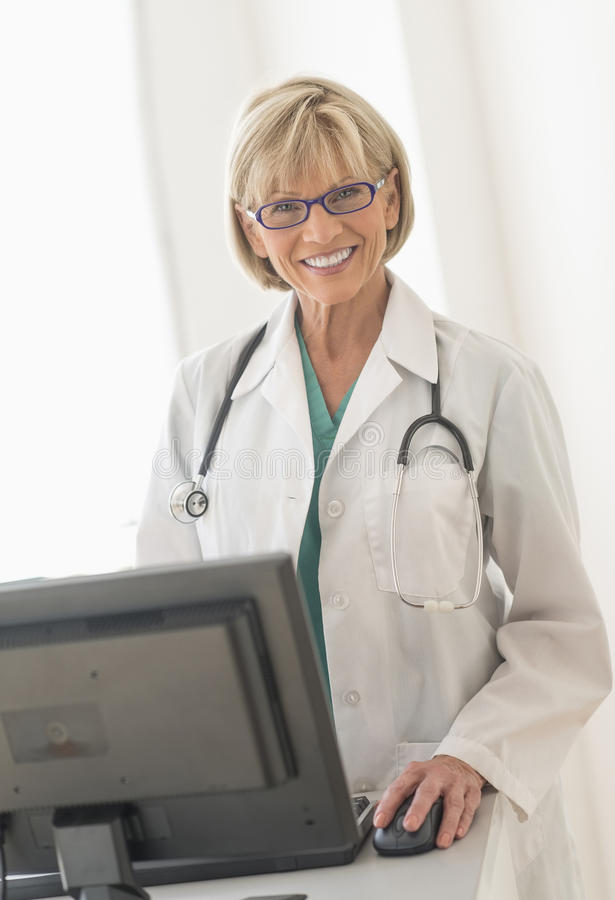 Happy Female Doctor Using Computer At Desk stock images
