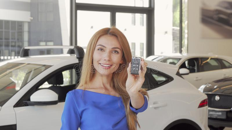 Happy female driver showing car key to the camera after buying new auto. Gorgeous woman looking excited, holding key to her newly bought automobile. Drive royalty free stock photo