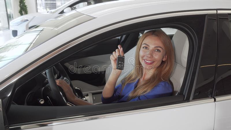 Happy female driver smiling holding car keys to her new automobile. Gorgeous woman sitting in a new car at the dealership, showing car keys. Ownership, driving stock photography