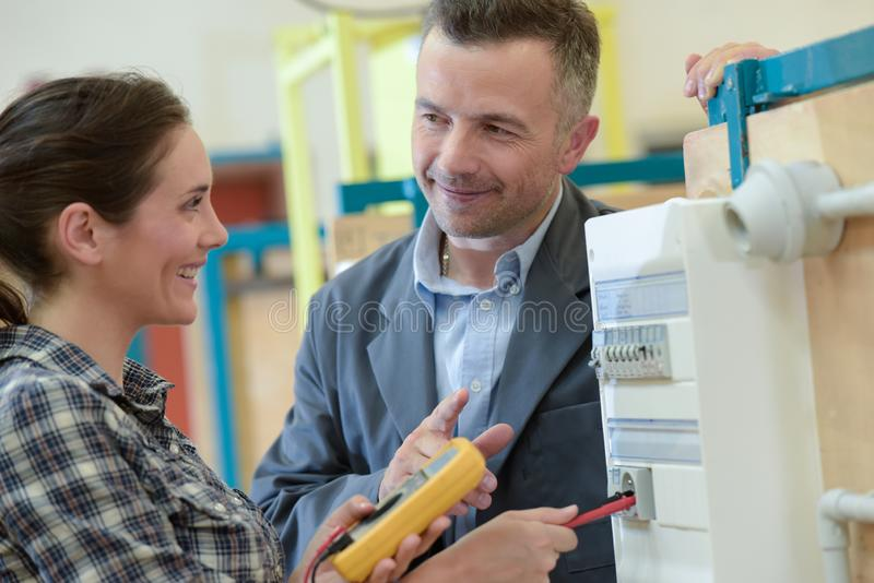 Happy female electrician using multimeter royalty free stock photos