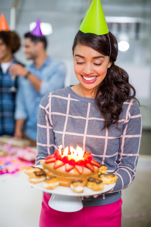Happy female executive wearing party hat and holding birthday cake royalty free stock images