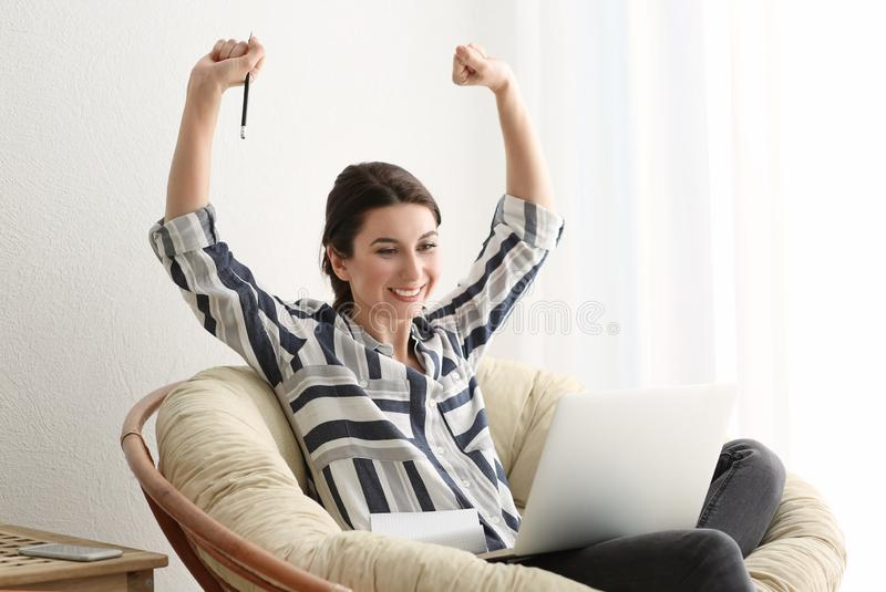 Happy female freelancer with laptop in lounge chair at home stock photography