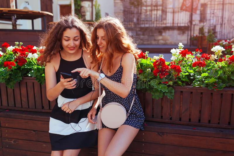Happy female friends checking social network using phone by cafe on city street. Girl pointing at smartphone stock image