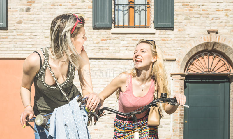 Happy female friends couple having fun riding bicycle in city. Old town - Friendship concept with young girlfriend on funny attitude biking together royalty free stock image
