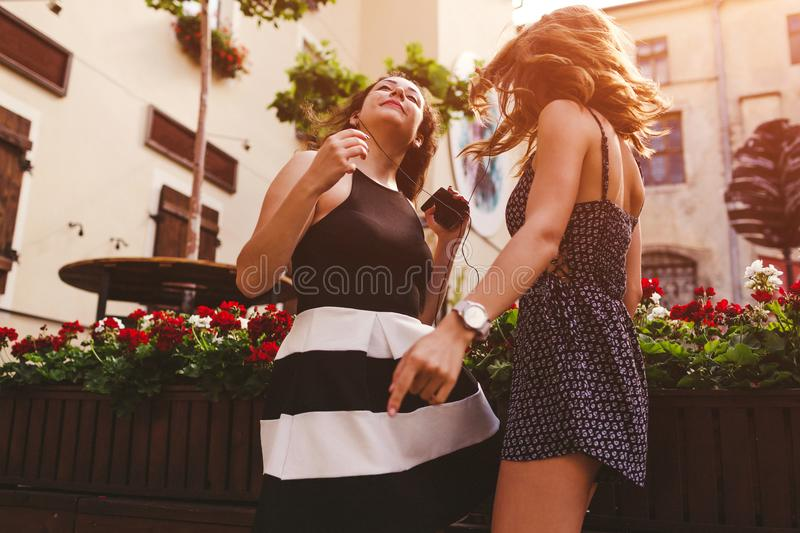 Happy female friends dancing while listening to the music outdoors stock images