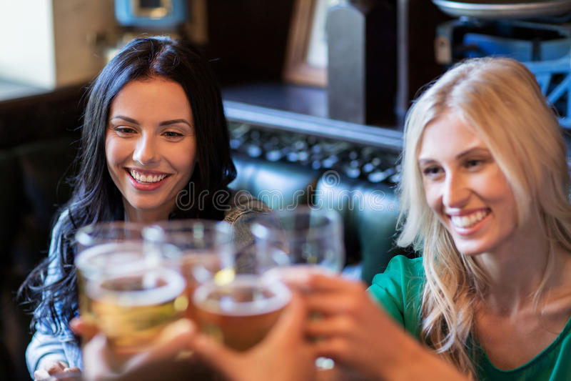 Happy female friends drinking beer at bar or pub stock photo
