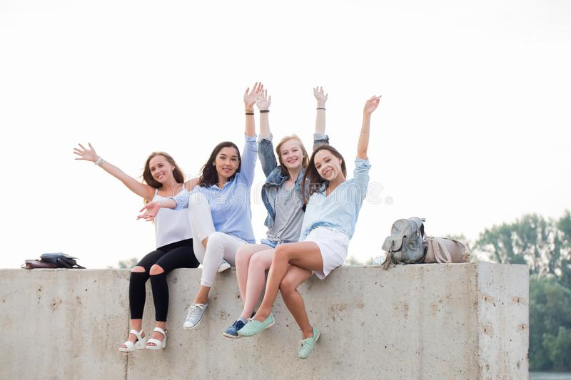 Happy female Friends Having Fun On Weekend, On Picnic Outdoors. Young Smiling People Sitting on concrete border stock photography