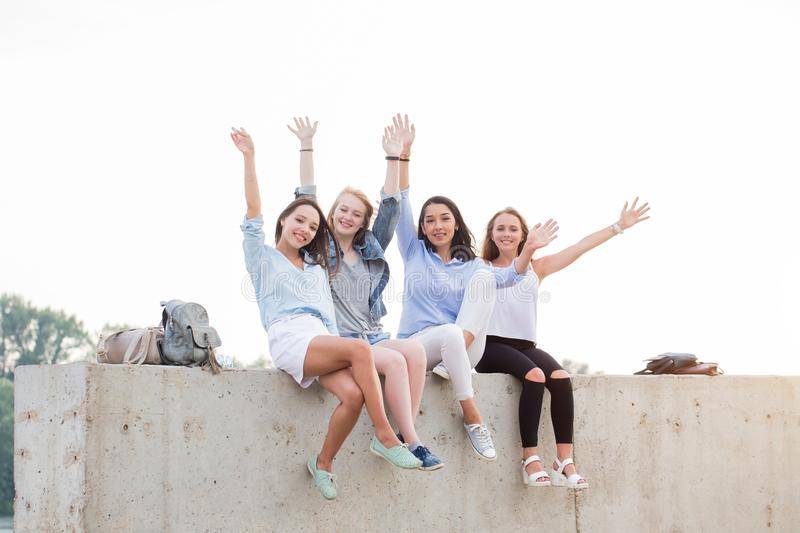 Happy female Friends Having Fun On Weekend, On Picnic Outdoors. Young Smiling student girls Sitting on concrete border royalty free stock image