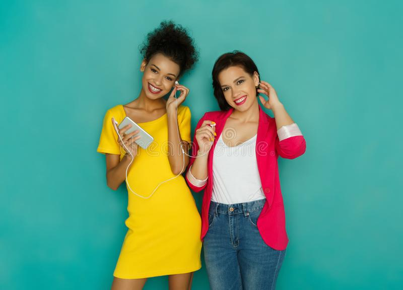 Happy female friends listen to music at studio background stock photos