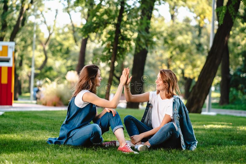 Happy female friends raising hands up giving high five in city park royalty free stock photos