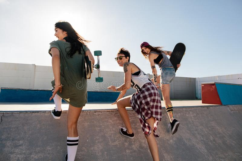 Happy female friends running over skateboard ramp royalty free stock photography