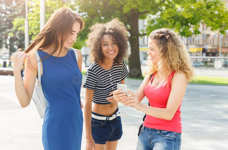 Happy female friends with smartphone outdoors stock image