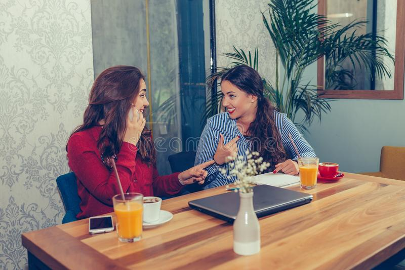 Happy female friends talking on phone and drinking coffee stock photos