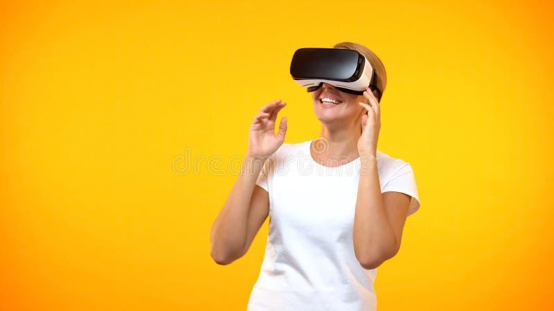 Happy female gamer wearing virtual reality headset, modern technology cyberspace royalty free stock photo