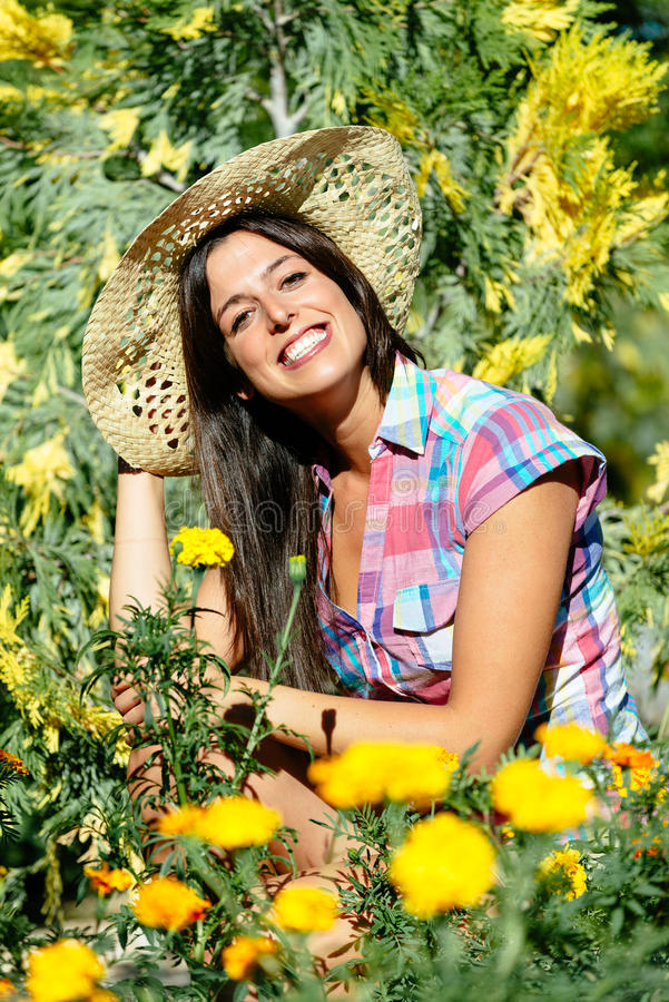 Happy female gardener and flowers. Female gardener surrounded by yellow flowers and plants. Successful woman enjoying her hobby stock photos