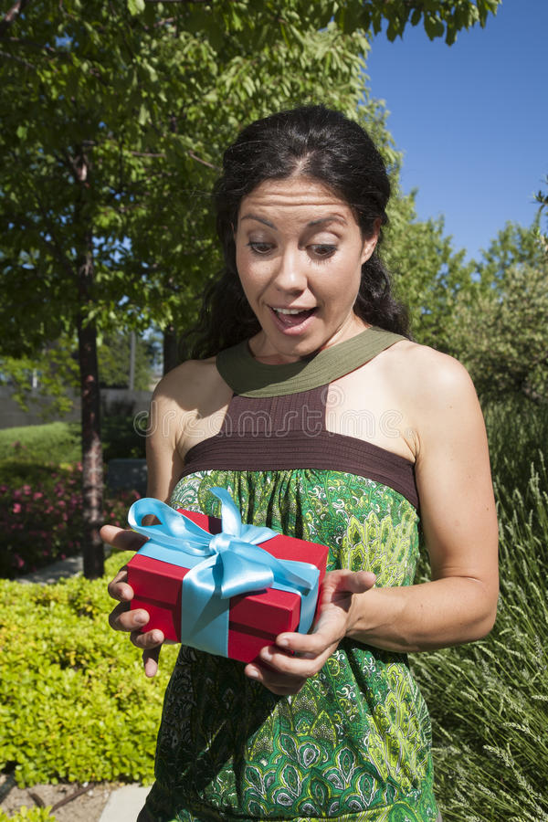Happy female with gift box. In exterior background stock photography