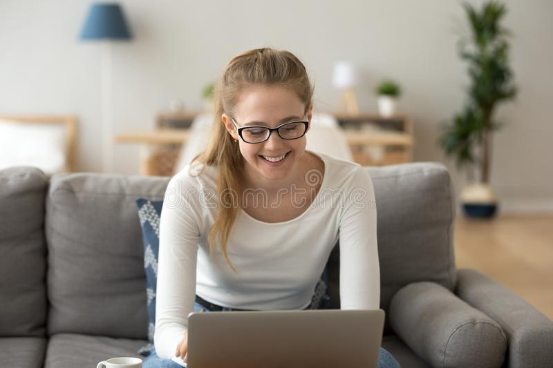 Happy female in glasses using laptop at home royalty free stock photo