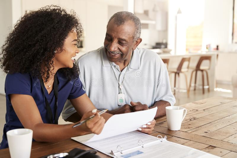 Happy female healthcare worker sitting at table smiling with a senior man during a home health visit. Happy female healthcare worker sitting at table smiling stock image