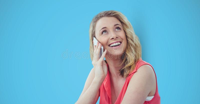Happy female hipster using smart phone against blue background stock photo