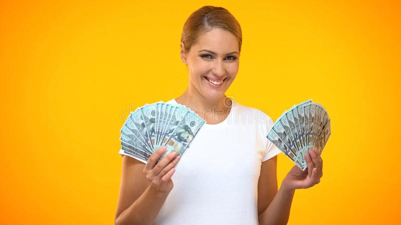 Happy female holding dollar banknotes, financial success, wealth earnings income royalty free stock photography