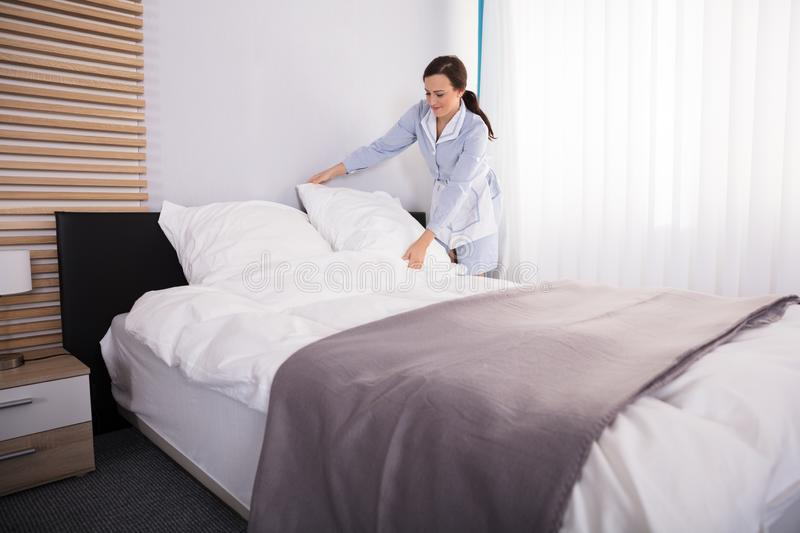Housekeeper Arranging Pillow On Bed. Happy Female Housekeeper Arranging Pillow On Bed In Hotel Room stock image