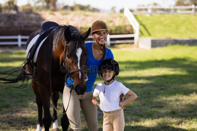 Happy female jockey with sister standing by horse stock images