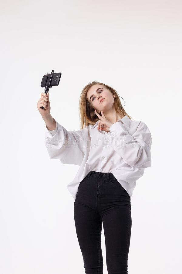 Happy young girl making self portrait with smartphone attached to small tripod royalty free stock photos