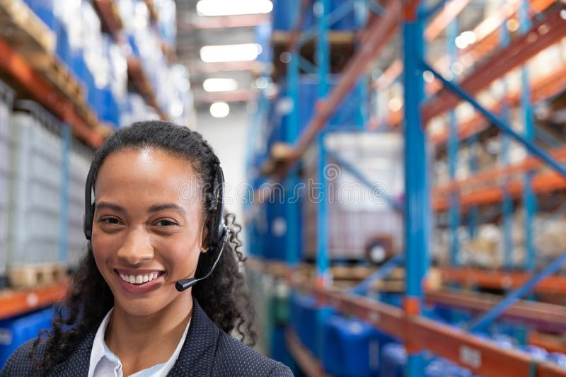 Happy female manager talking on headset in warehouse. Close-up of happy female manager talking on headset in warehouse. This is a freight transportation and royalty free stock images