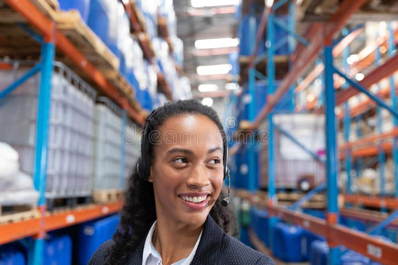 Happy female manager talking on headset in warehouse. Close-up of happy female manager talking on headset in warehouse. This is a freight transportation and stock images