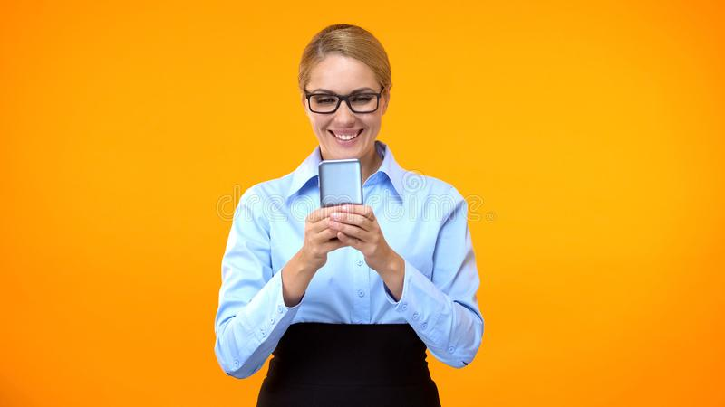 Happy female manager typing message on smartphone, social networks, business app. Stock photo stock photography