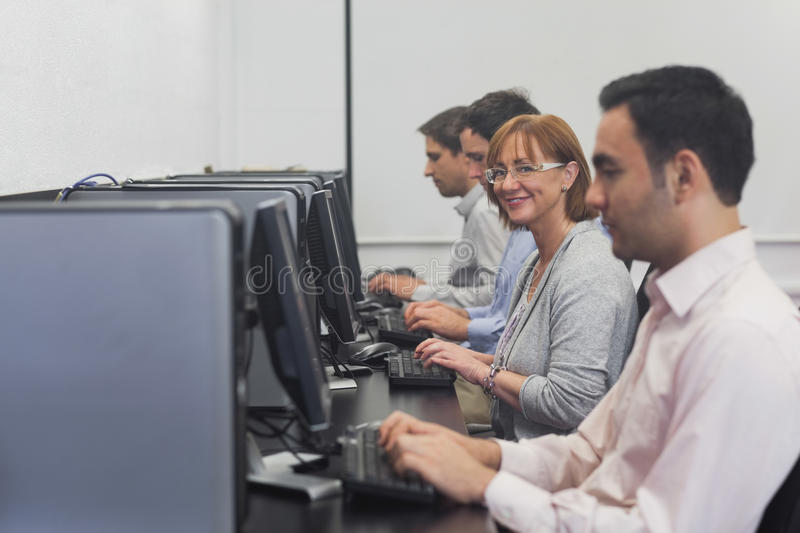 Happy female mature student sitting in computer class