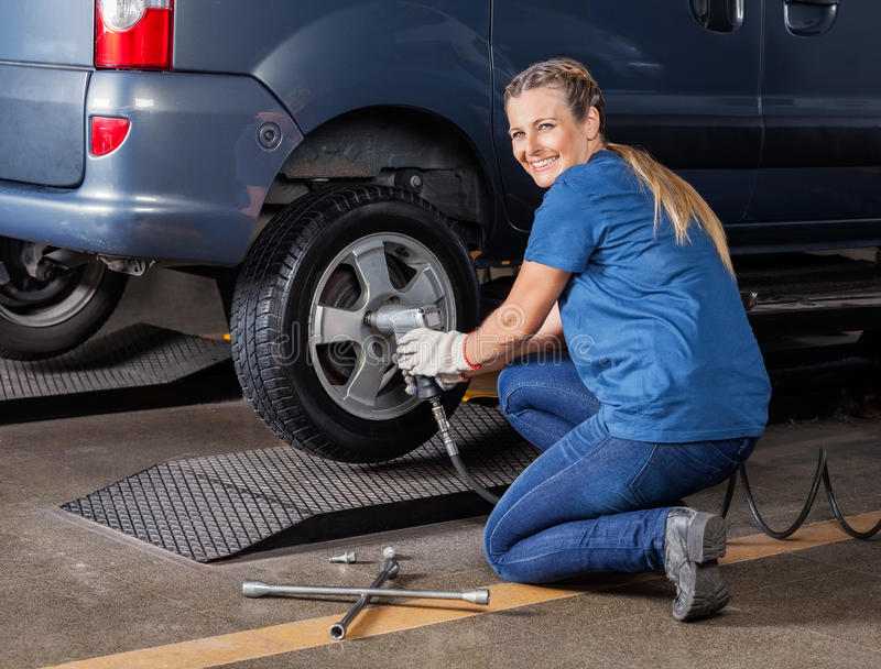 Happy Female Mechanic Fixing Tire With Pneumatic Wrench. Portrait of happy female mechanic fixing car tire with pneumatic wrench at auto repair shop stock images