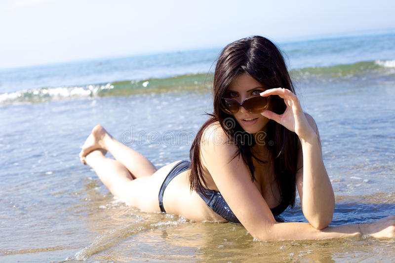 Happy female model with sun glasses playing in water royalty free stock photography
