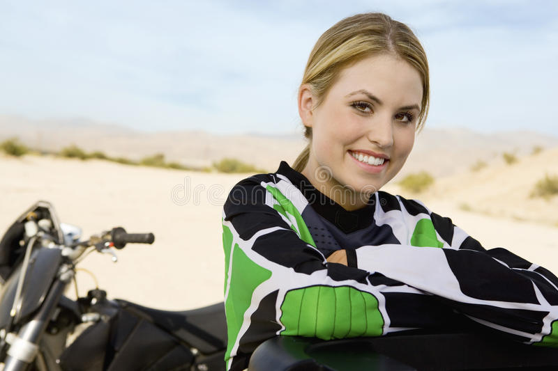 Happy Female Off Road Motor Biker. Portrait of happy female off road motor biker with hands folded stock photo