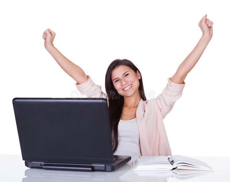 Happy female office worker rejoicing. Happy beautiful vivacious female office worker or businesswoman rejoicing raising her hands high in the air royalty free stock image