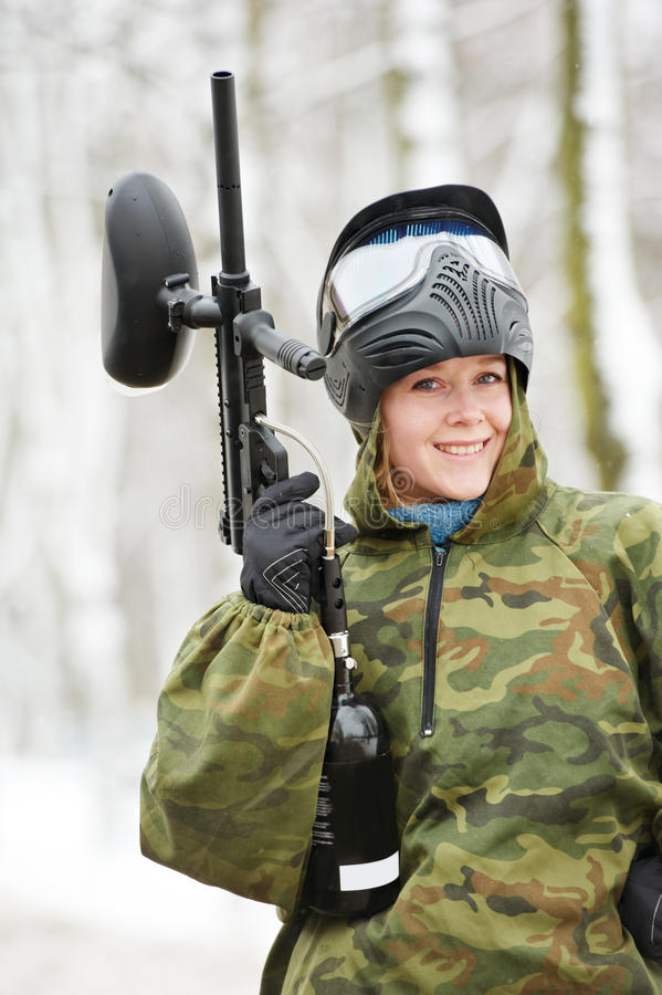 Happy female paintball player with marker at winter outdoors royalty free stock photography