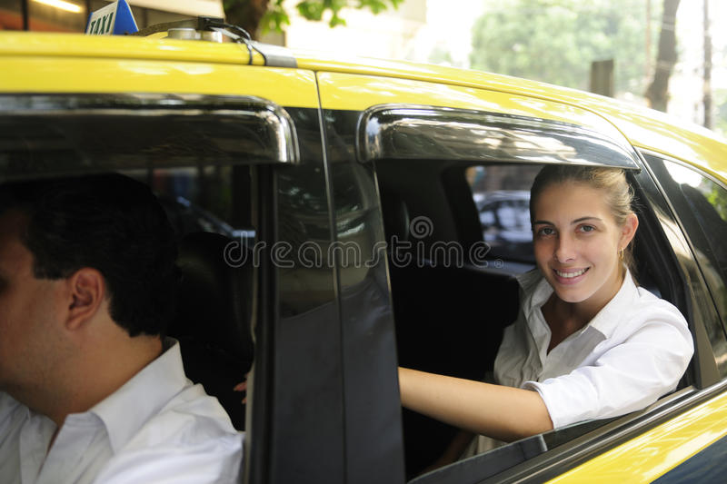 Happy female passenger inside of a taxi. Urban transport: happy female passenger inside of a taxi stock image