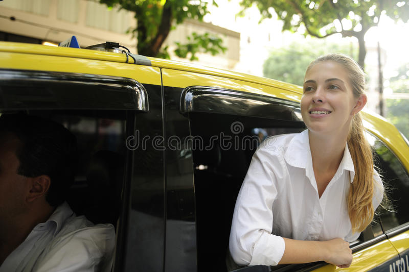 Happy female passenger inside of a taxi. Urban transport: happy female passenger inside of a taxi stock photography