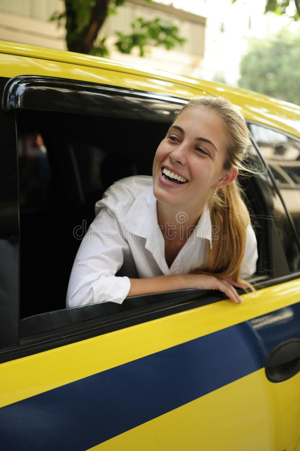 Happy female passenger inside of a taxi. Urban transport: happy female passenger inside of a taxi royalty free stock photo