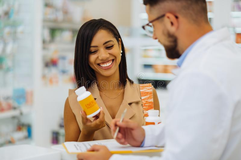 Happy female person looking at pills for skincare royalty free stock images