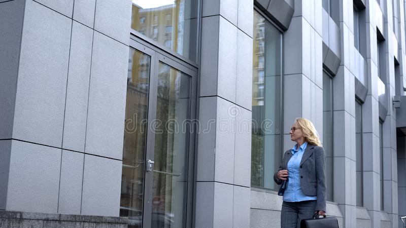 Happy female politician admiring reflection in office building glass, career. Stock photo stock image